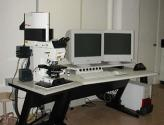Picture of a white Leica DM RE microscope connected to a white Leica TCS SP2 system with two monitors