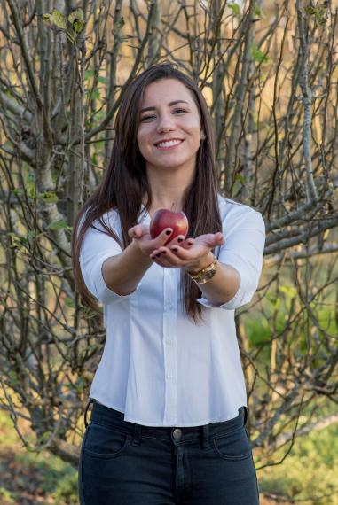 A photo of Leticia Reis standing in front of a wooded area holding a red apple in outstretched hands.