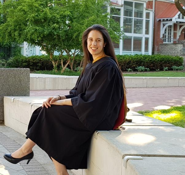 Photo of Anna Schwanke sitting on a stone bench wearing graduation robes.