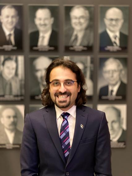Omid Norouzi, wearing a suit, glasses and striped tie, smiles in front of a blurred-out background of portraits.