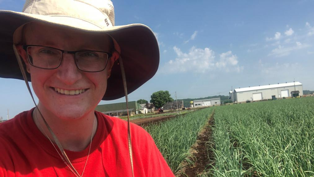 Sara Stricker in the field with the onions