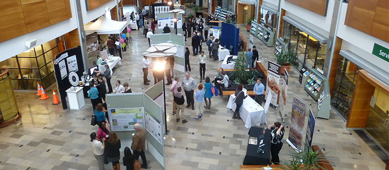 Image taken from above of people attending an event looking at booths and scientific posters
