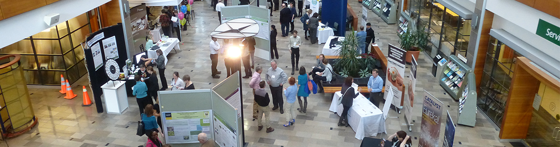 Image taken from above of people at an event inside a building visiting booths and reading scientific posters