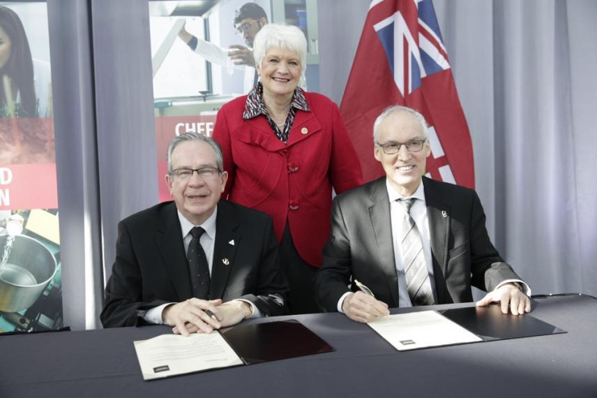 Minister Jeff Leal, MPP Liz Sandals, and UofG President Franco Vaccarino sitting in front of newly signed agreements