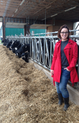 Dr. Christine Baes stands in hay at the dairy barn