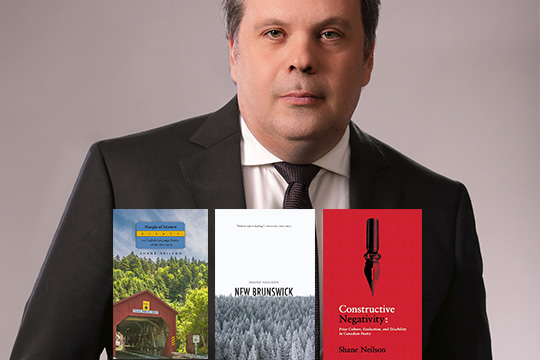 Author Shane Neilson, in a suit, with the covers of his three most recent books.