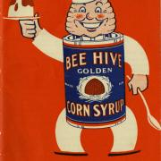 Red cookbook cover with a cartoon character with a bee hive head advertising corn syrup.