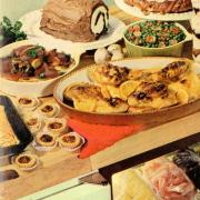 Cookbook cover with roast chickens, veggies, tarts, and dessert roll on a table.