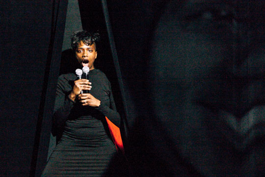 Image of Aisha Sasha John on stage in front of a black curtain with a microphone.