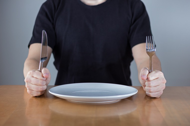 A person sitting at a dining table holding a knife and fork with a plate in between