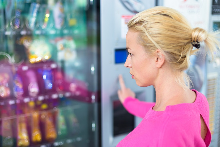 A woman looking at a vending machine