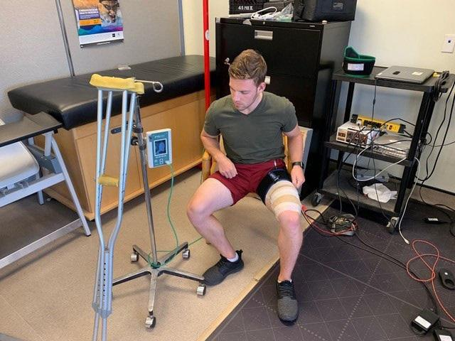 A study participant receiving blood flow restriction and electrical muscle stimulation to prevent muscle atrophy (photo courtesy of J. Burr)
