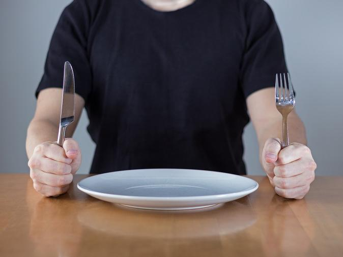 A person sitting at a dining table holding a fork and knife with a plate in between