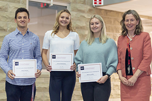 Three students stand with the dean of CEPS with their awards