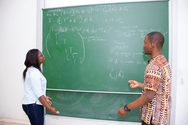 Two students working on a chalkboard