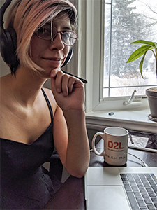Zina Ramirez working from home with headphones on and D2L mug nearby.