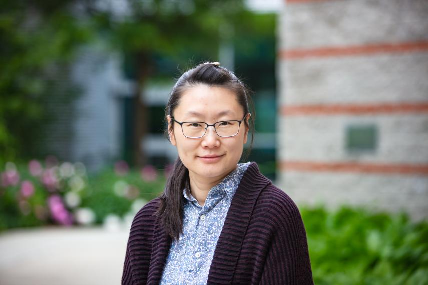 Prof. Emily Chiang in front of grey building with gardens