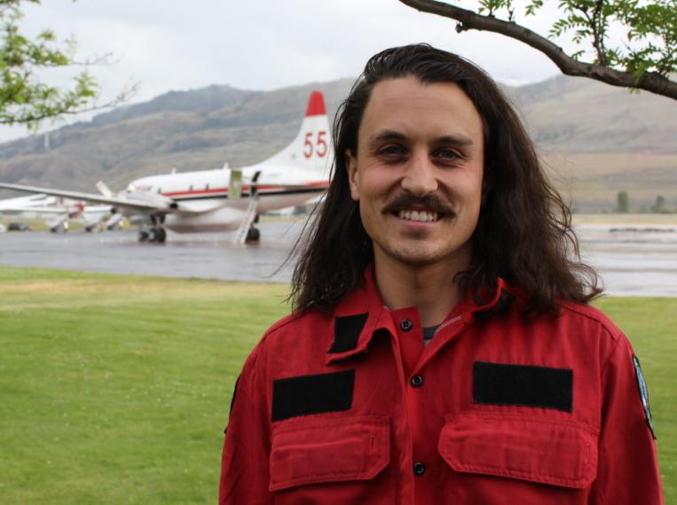 Portrait of Bryan Moreira with a plane in the background