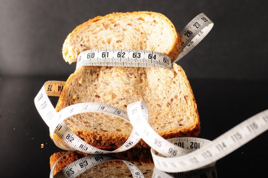 Slice of bread with measuring tape wrapped around it