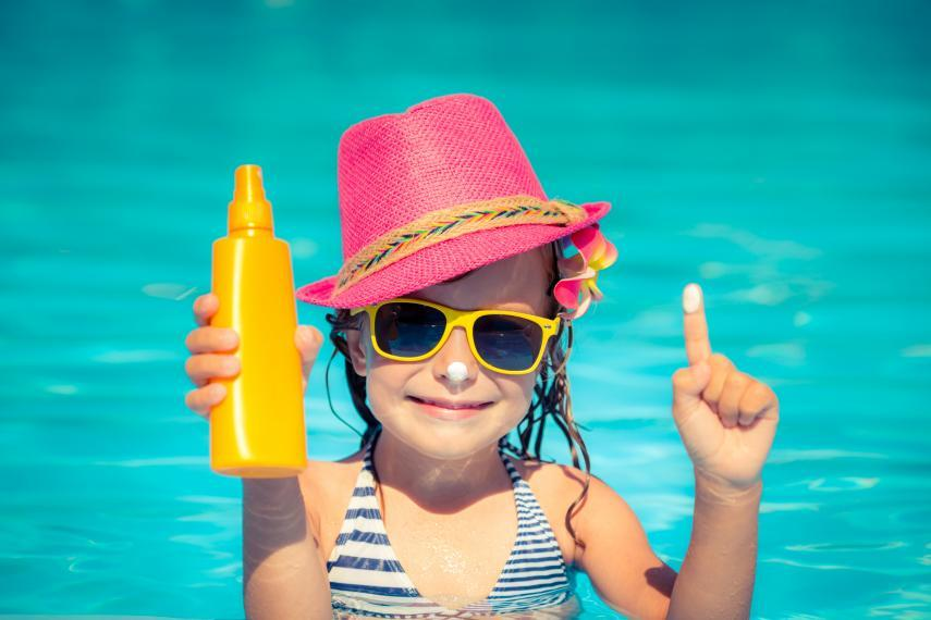 Child in a swimming pool holding sunscreen