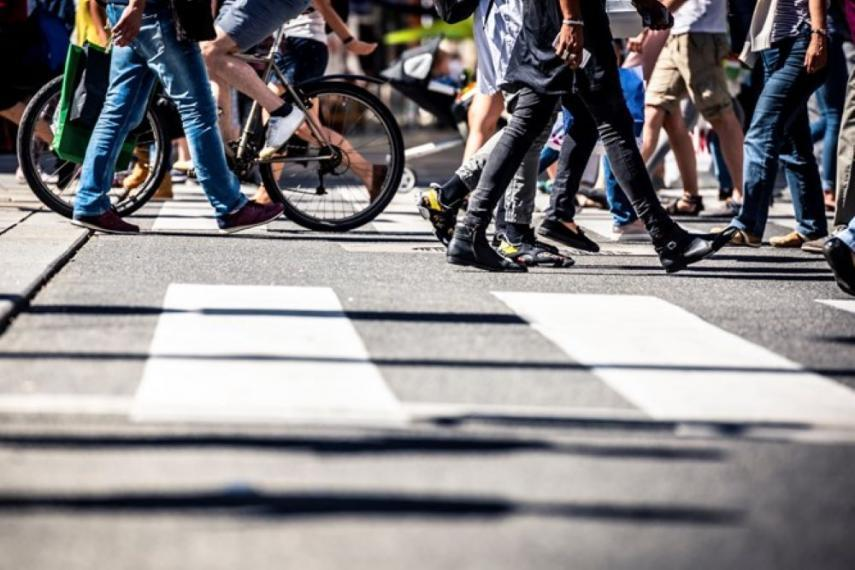 Image of a crowd of people crossing the street, only visible from the waist down