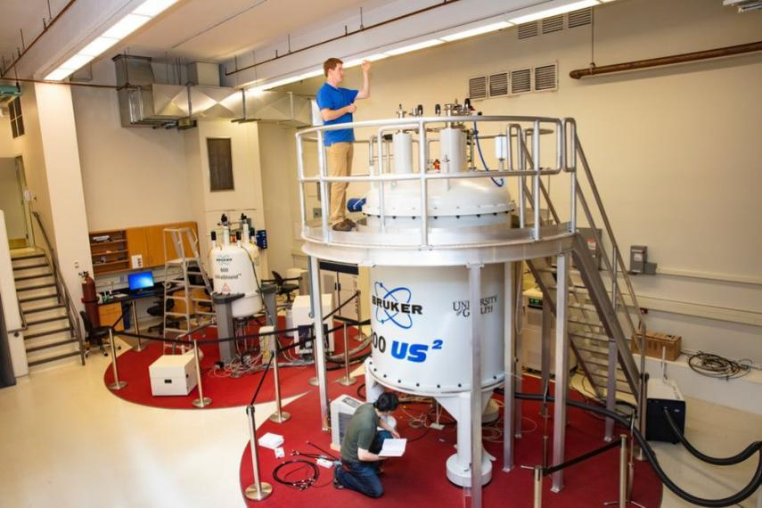 Image of students working at NMR machine.