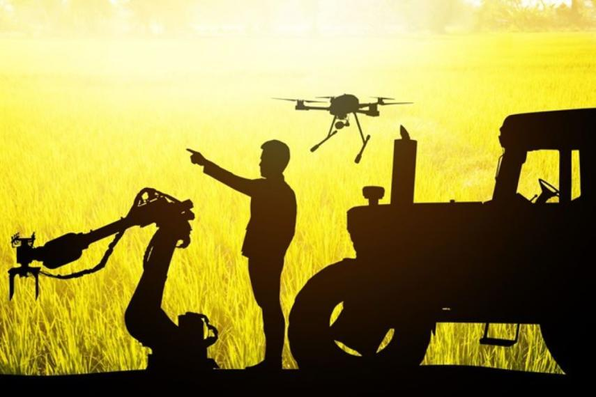 Silhouette image of a person and robotic equipment on a farm including a drone and a tractor