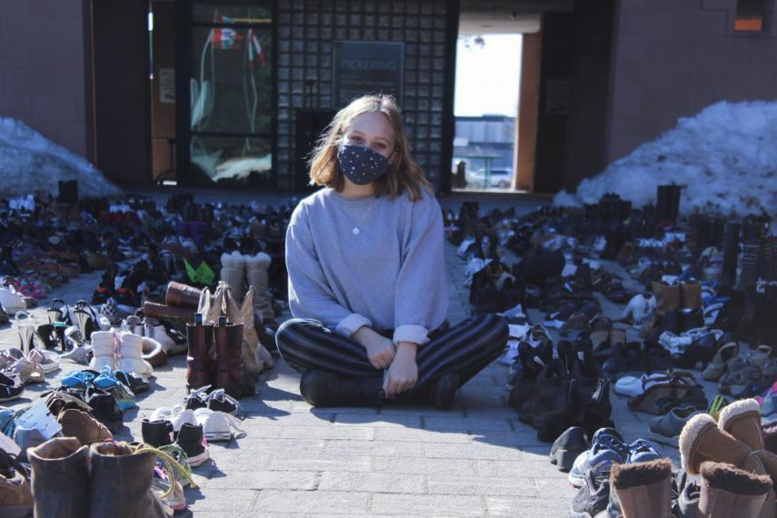 Ally Zaheer sits cross-legged wearing a mask and surrounded by hundreds of pairs of shoes outside city hall in Pickering
