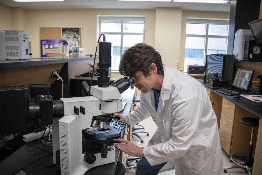 Image of Jay Leitch looking into equipment in nanoscience lab