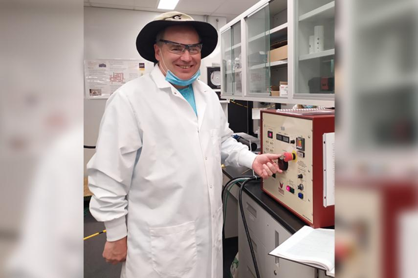 Dr. Kevin Keener standing in laboratory next to a cold plasma generator.