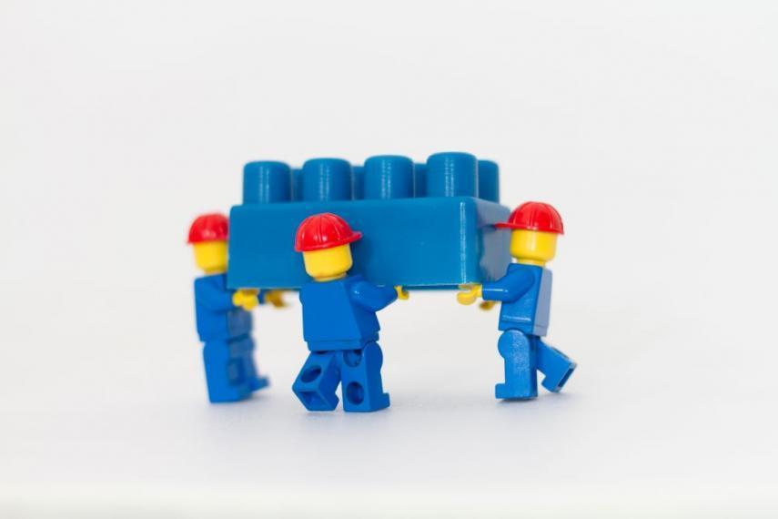 Three LEGO construction figurines carrying a LEGO brick