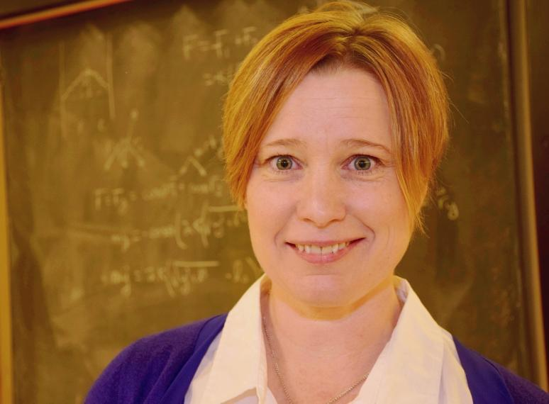 Physics professor Joanne O'Meara in front of a chalkboard.