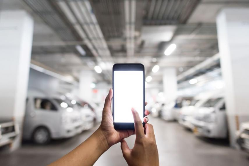 Photograph of an underground parking lot with a person's hands holding a smart phone