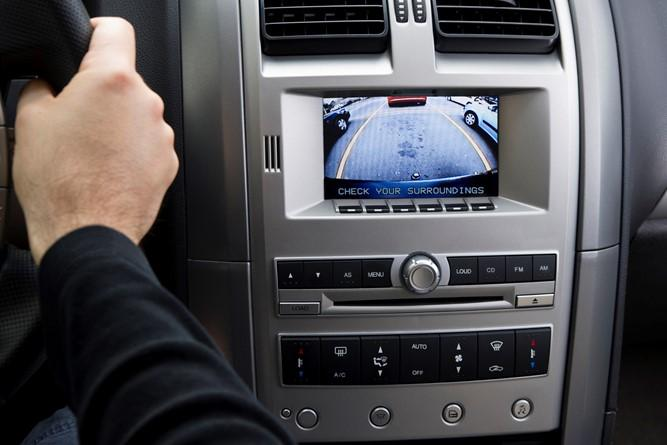 Image of a vehicle rearview camera with a hand on a steering wheel.