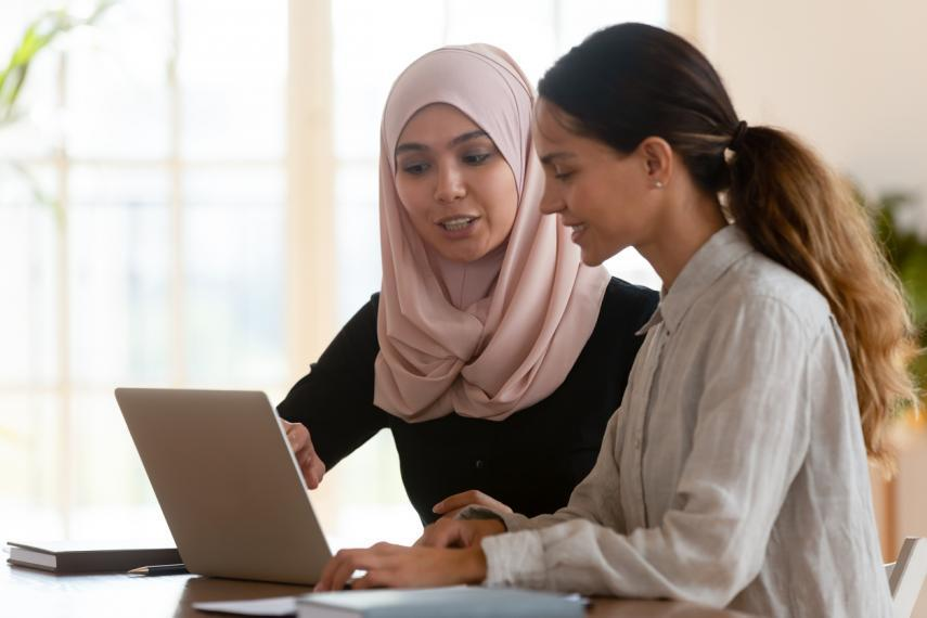 Stock image of two women working together while looking at a computer