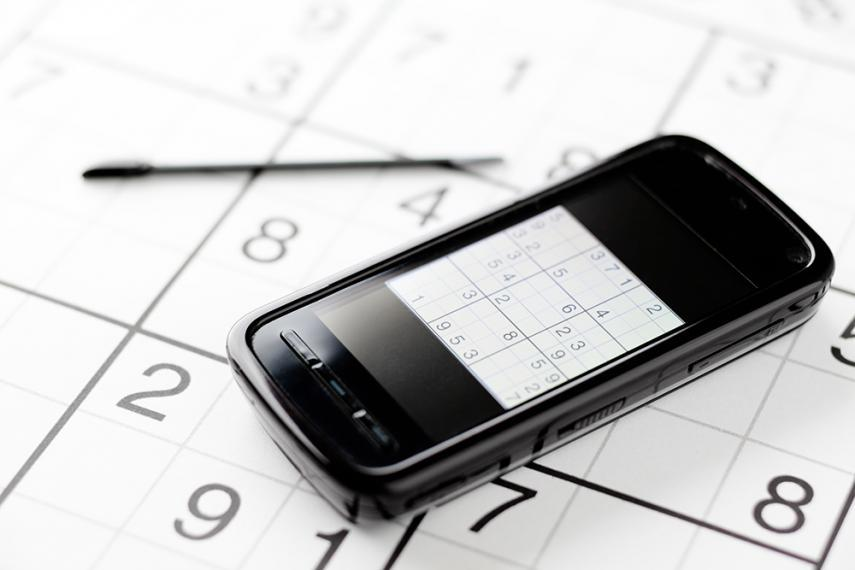 iPhone sitting on sudoku puzzle with pen in background
