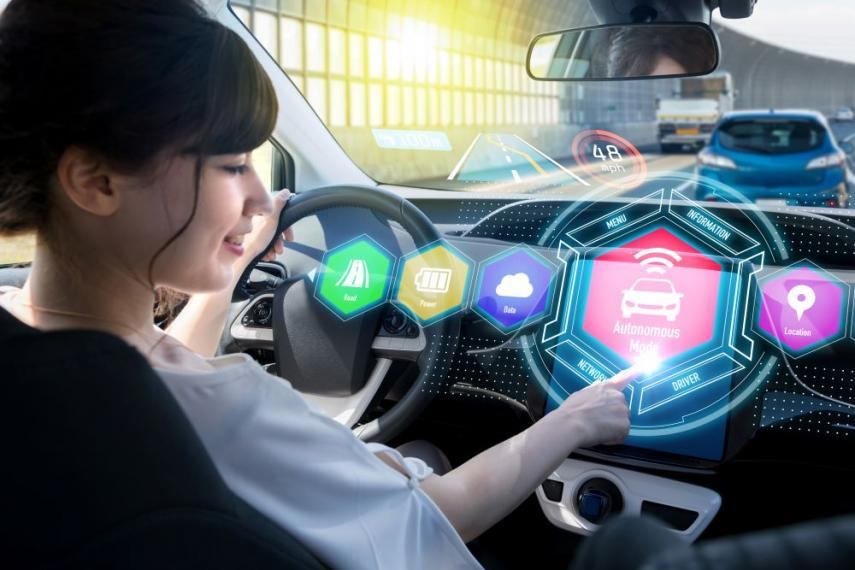 Woman sitting in self-driving car with colourful, stylized screens in front of her.
