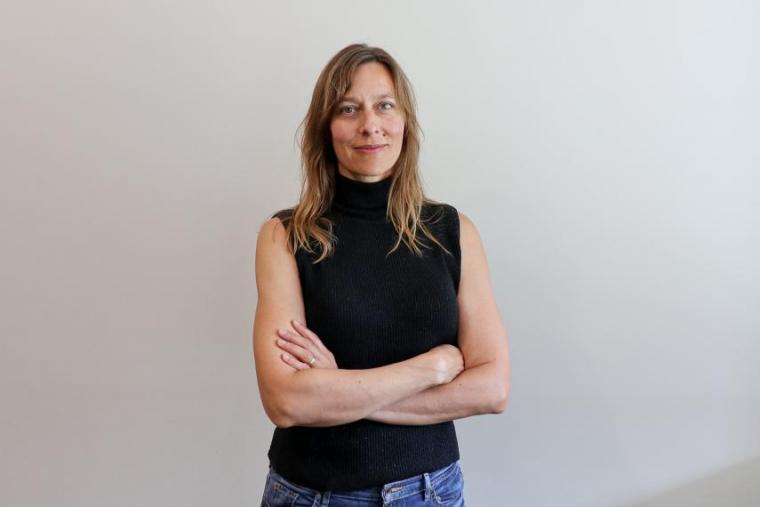 Kathryn Preuss standing and smiling against neutral backdrop with arms crossed