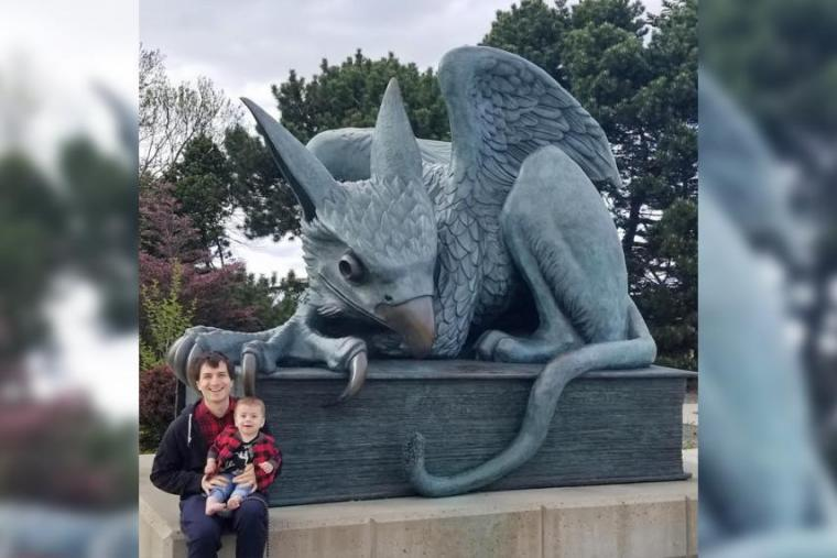 Dr. Mihai Nica and his young son sitting in front of the Gryphon statue on U of G campus.
