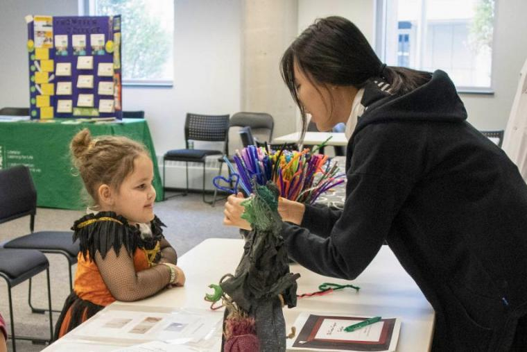 Volunteer leans over desk and shows younger school-aged girl science activity