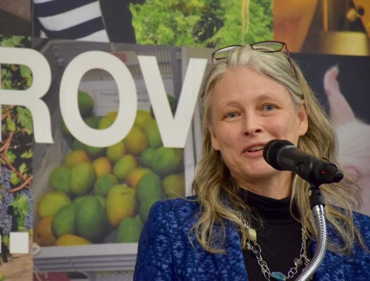 Image of Andrea Bradford talking into microphone in front of Improve Life banner