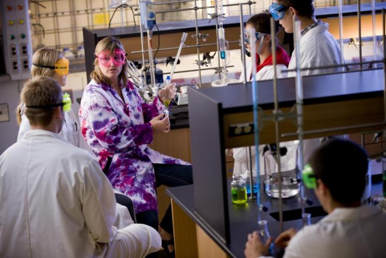 Bonnie Lasby sits in a lab and shows students a science demonstration. They are standing around her in personal protective equipment
