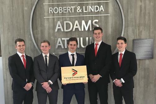 Image of Forward Innovation team against Robert & Linda Adams Atrium sign in Thornborough