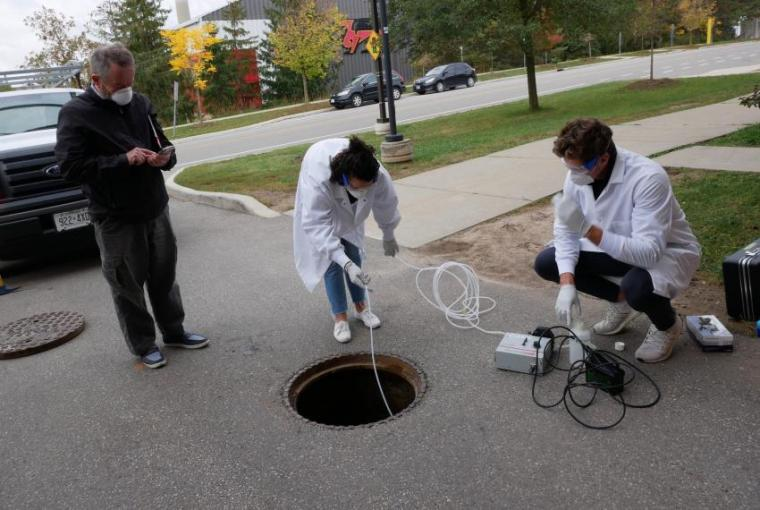 Engineering prof. Ed McBean stands to the left of two student research assistants Jonathan Evans and Melissa Novacefski. McBean is looking at data on his phone while the students are squatted over a manhole with the cover removed, using equipment to collect samples.