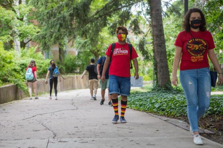 Image of students walking on campus wearing U of G gear and masks while physical distancing