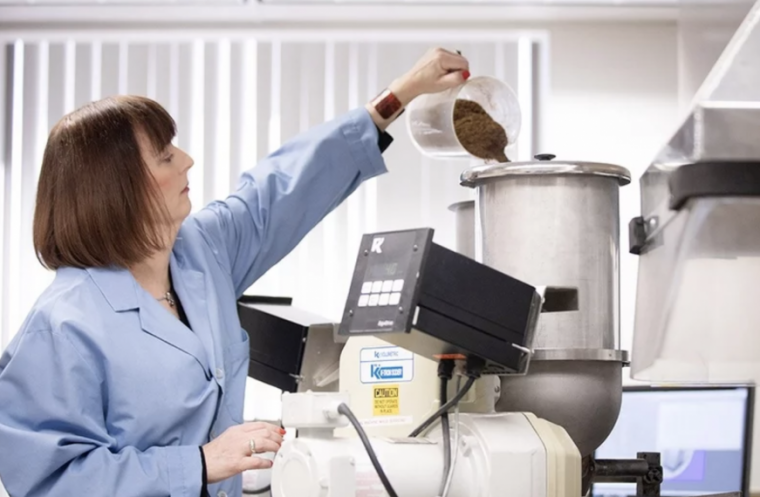 Image of woman pouring coffee beans into machine