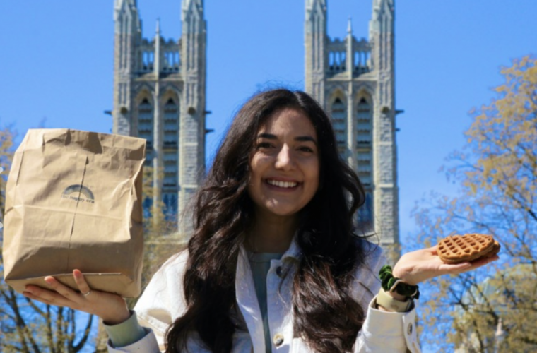 Domenique Mastronardi holding her waffle creation while standing in front of the Basilica of Our Lady Immaculate in downtown Guelph