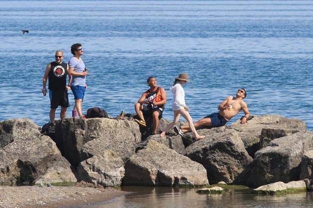 Image of young people lounging and socializing on rocks with water in background and beach in foreground