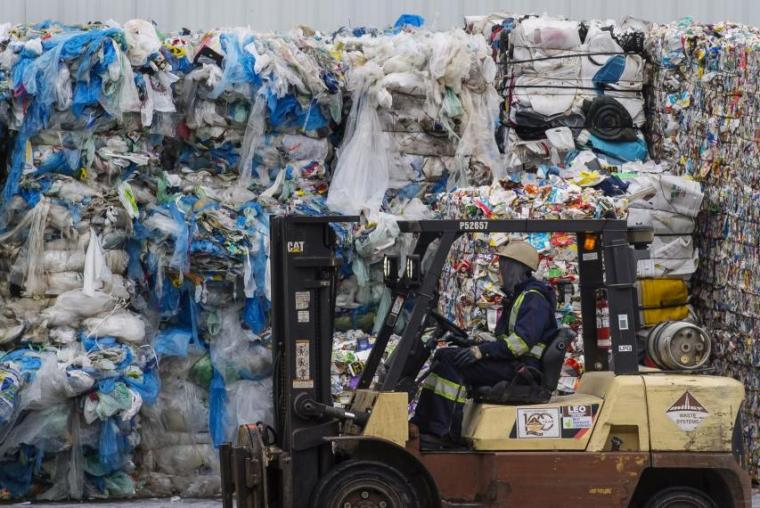 Image of plastic waste pile with forklift in front