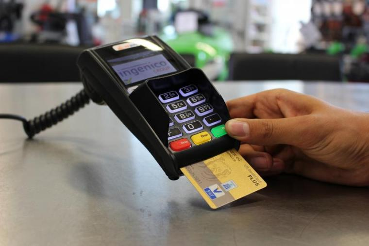 Image of person's hand holding pay terminal with debit or credit card inserted